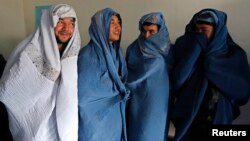 Male Afghan women's rights activists pose for media as they wear burqas to show their solidarity to Afghan women ahead of International Women's Day in Kabul, March 5, 2015.