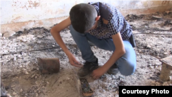 Noeh Binoo, 13, squats to collect remains of his marbles in what used to be his bedroom before Islamic State militants torched it three years ago, Aug. 2017. (Open Doors USA photo)