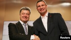 Ukrainian businessman, politician and presidential candidate Petro Poroshenko (L) and heavyweight boxing champion and Ukrainian Democratic Alliance for Reform party leader Vitali Klitschko shake hands during a rally at Poroshenko's election headquarters i