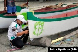 In this April 2, 2019, photo, a member of Islamic Defenders Front paints their group's logo as they help local fishermen to build boats at a fishing village affected by the 2018 tsunami in Palu, Central Sulawesi, Indonesia.
