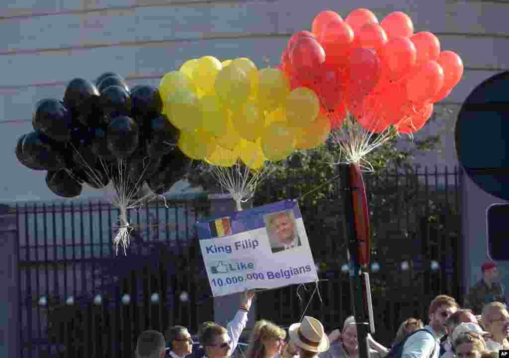 Globos inflables con los colores de la bandera de Bélgica son desplegados frente a la catedral St. Gudule para saludar al nuevo monarca, una idea creada con la finalidad de mostrar un cartel inspirado en la página de Facebook de Felipe.