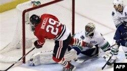 Форвард «Chicago Blackhawks» Брайан Бикел забивает шайбу в ворота ванкуверских «Касаток»