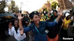 Mutane suna waka suna girmama Nelson Mandela yayin da yake jinya