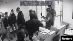 This video grab from a security camera shows the moment where armed police break in to Voluntad Popular (Popular Will) headquarters in Caracas, Feb. 17, 2014. Videos sent to media by Popular Will, which could not be independently identified, showed men entering the premises waving guns and trying to kick down a door.