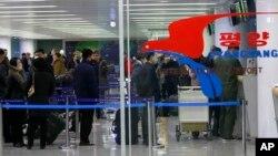 Hành khách đeo khẩu trang chờ chuyến bay đến Vladivostok, Nga, tại phi trường quốc tế Bình Nhưỡng, Triều Tiên, vào ngày 9/3/2020.