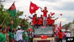 Supporters of the National League for Democracy (NLD) party on a motorcade pass supporters of the opposition Union Solidarity and Development Party (USDP), seen at left, during a campaign in Wundwin, near Mandalay on September 19, 2020. (Photo by Kyaw The