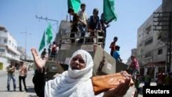 一位巴勒斯坦妇女站在以色列军事装备前面做手势。