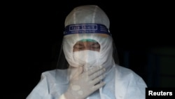 A volunteer wearing a protective suit adjusts his face mask before carrying a dead body amid the outbreak of the coronavirus disease (COVID-19), in Yangon, Myanmar, October 4, 2020. REUTERS/Shwe Paw Mya Tin