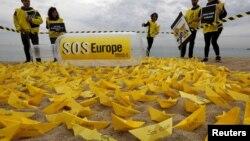 """Des bénévoles de Amnesty International ont installé des bateaux en papier avec le slogan """"SOS Europe"""" sur les plages espagnoles de San Sebastian à Barcelona, 22 avril 2015."""