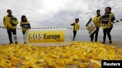 """Tình nguyện viên thuộc Tổ chức Ân xá quốc tế đặt hàng trăm chiếc thuyền giấy với hàng chữ """"SOS Châu Âu"""" trên bãi biển San Sebastian ở Barcelona, Tây Ban Nha để nêu bật cuộc khủng hoảng nhập cư ở Địa Trung Hải, với hàng trăm di dân đã chết đuối trên đường vượt biển đến châu Âu."""