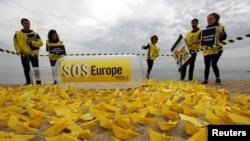 """Voluntarios de Amnistía Internacional colocan botes de papel con el letrero """"SOS Europa"""" en una playa de San Sebastián, en el norte de España."""