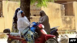 FILE - Women chatting while sitting on their bikes in a district of Maroua, northern Cameroon.