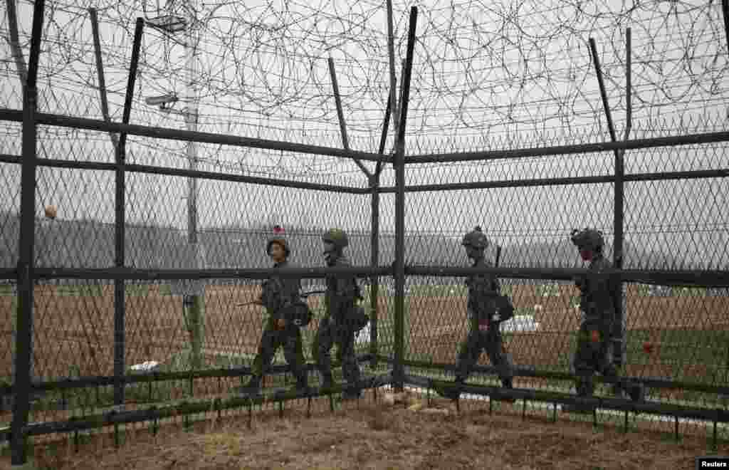 South Korean soldiers patrol along a barbed-wire fence, near the demilitarized zone that separates the two Koreas in Paju, north of Seoul, April 5, 2013.