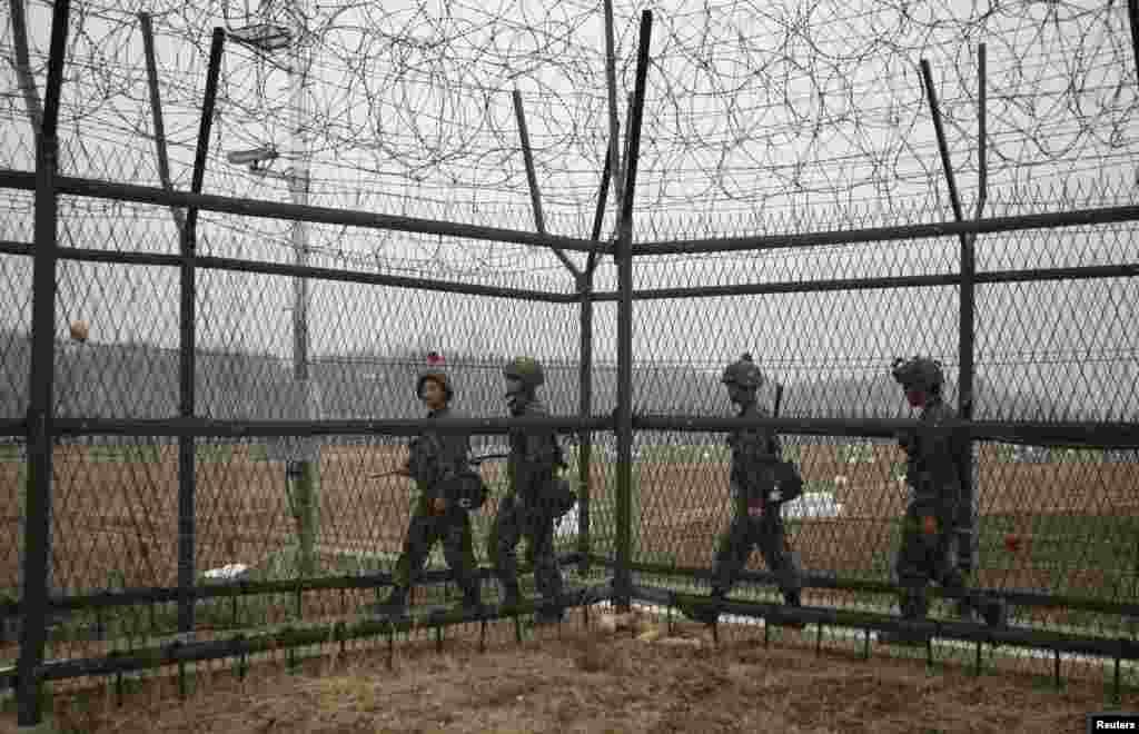 Cənubi Koreya əsgərləri iki Koreyanı ayıran Seuldan şimalda Pacu qəsəbəsi yaxınlığındakı demilitarizasiya zonasında patrul çəkirlər. 5 aprel, 2013.