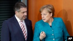 FILE - German Chancellor Angela Merkel, right, and German Foreign Minister Sigmar Gabriel, left, arrive for the weekly cabinet meeting at the Chancellery in Berlin, April 12, 2017.