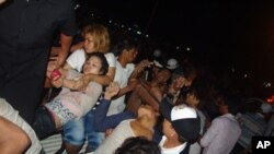 """Victims of a deadly stampede are carried onto a rescue truck in Phnom Penh, in what Cambodian Prime Minister calls the country's """"worst tragedy"""" since the Khmer Rouge period."""
