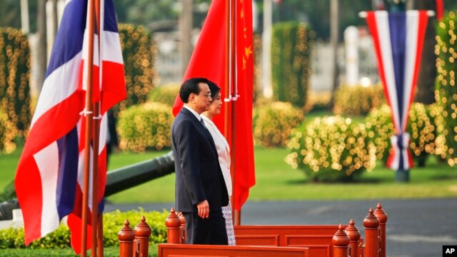 Thailand's Prime Minister Yingluck Shinawatra and China's Premier Li Keqiang listen to national anthems during welcoming ceremony, government house, Bangkok, Oct. 11, 2013.