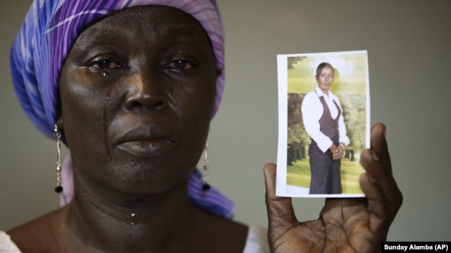 In this Monday, May 19, 2014 file photo, Martha Mark, the mother of kidnapped school girl Monica Mark cries as she displays her photo, in the family house, in Chibok, Nigeria.