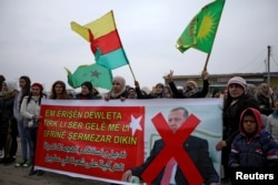 "FILE - People hold flags and carry a banner reading, ""We condemn and denounce the attacks of the Turkish government against our people in Afrin,"" during a protest against Turkish attacks on Afrin, in Hasaka, Syria, Jan. 18, 2018."