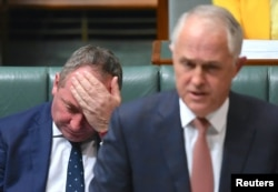FILE - Australian Deputy Prime Minister Barnaby Joyce reacts as he sits behind Australian Prime Minister Malcolm Turnbull in the House of Representatives at Parliament House in Canberra, Australia, Oct. 24, 2017.