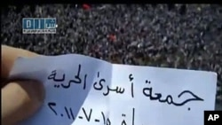 An image taken from footage uploaded on YouTube by the Shams News Network (SNN) shows a Syrian anti-government protester holding a piece of paper which says in Arabic 'Friday of Prisoner Freedom, Hama, July 15, 2011' on a rooftop above thousands of people