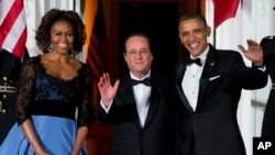First lady Michelle Obama, left, and President Barack Obama welcome French President François Hollande for a State Dinner at the North Portico of the White House on Tuesday, Feb. 11, 2014.