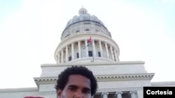 El artista Luis Manuel Otero Alcántara posa con la bandera cubana desde el Capitolio de La Habana, actual sede del parlamento de Cuba. {Foto cortesía MSI]