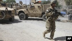 A US soldier, part of the NATO forces, patrols a police station after it was attacked by militants, Kandahar, Afghanistan, June 19, 2012.