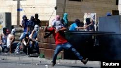 Seorang warga Palestina melemparkan batu ke arah polisi Israel dalam bentrokan di Shuafat, wilayah sub-urban Arab di Yerusalem (2/7).