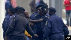 An unidentified journalist from an opposition television station is detained and roughed up by police while covering an opposition protest in Kinshasa, Congo on Thursday, Sept. 1, 2011.