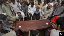 Relatives and colleagues carry the casket of Pakistani journalist Saleem Shahzad for burial after funeral prayers in Karachi, June 1, 2011