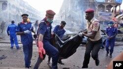 Petugas penyelamat Nigeria mengangkut korban tewas dalam ledakan bom di sebuah mall yang ramai di Abuja, Rabu (25/6).