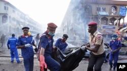 Para petugas penyelamat membawa jenazah korban pemboman mal di Abuja, Nigeria (25/6). (AP/Olamikan Gbemiga)