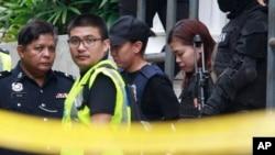 Terdakwa Siti Aisyah (dua dari kanan) dikawal ketat polisi saat keluar dari gedung pengadilan di Sepang, Malaysia, 1 Maret 2017. (AP Photo/Daniel Chan)
