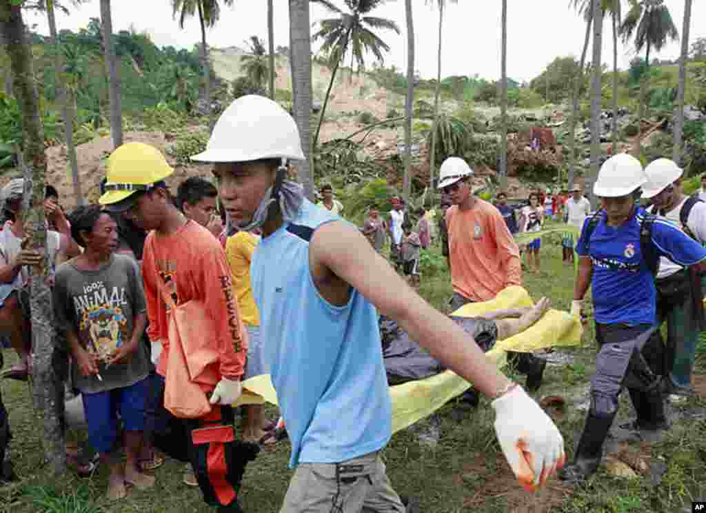 Rescuers carry a body retrieved from a landslide caused by an earthquake in La Libertad, Negros Oriental in central Philippines February 7, 2012. (Reuters)