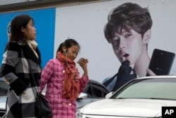 Chinese women walk past advertisement featuring teen idol Lu Han, also known as China's Justin Bieber in Beijing. (AP Photo/Ng Han Guan, File)