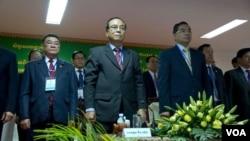 Election reform working group co-chairs Bin Chhen (center) of the Cambodian People's Party (CPP) and Kuoy Bunroeun (right) of the Cambodia National Rescue Party (CNRP) stand up at the opening of a national workshop on two new election draft laws on Monday, March 9, 2015 at the National Assembly before the discussion. (Neou Vannarin/VOA Khmer)