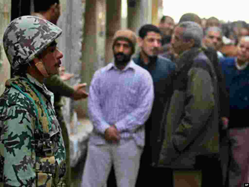 An Egyptian soldier stands guard as voters wait outside a polling center south of Cairo on November 28, 2011. (AP)
