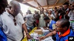 Presiden Ghana John Dramani Mahama (kiri) memberikan suara di TPS di Bole, Ghana, Rabu (7/12).