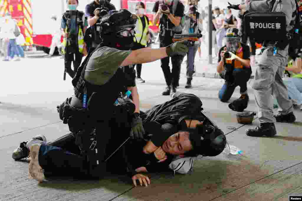 A police officer raises his pepper spray gun as he detains a man during a march against the national security law at the anniversary of Hong Kong's handover to China from Britain.