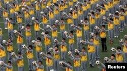 Học sinh tập thể dục buổi sáng với bóng đá tại trường tiểu học ở Lâm Hải, tỉnh Chiết Giang, ngày 26/3/2015.