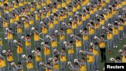 FILE - Students do morning exercises with soccer balls on a playground at a primary school in Linhai, Zhejiang province, March 26, 2015.