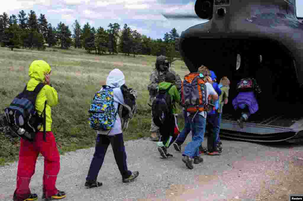 Children board a rescue helicopter flown by the U.S. Air National Guard after severe flooding shut down major roads leading out of Jamestown, Colorado, Sept. 14, 2013. (U.S. Air National Guard Handout photo)