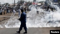 FILE - A policeman walks away after throwing a tear gas canister during a protest against Burundian President Pierre Nkurunziza and his bid for a third term in Bujumbura, June 2, 2015.