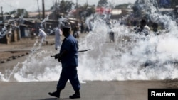 FILE - A policeman walks away after throwing a teargas canister during a protest against Burundi President Pierre Nkurunziza and his bid for a third term in Bujumbura, Burundi, June 2, 2015.