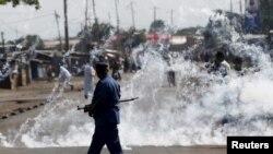 Un policier va se mttre à l'abri après avoir lancé des grenades lacrymogènes aux manifestants à Bujumbura, Burundi, le 2 juin 2015.