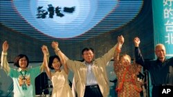 Taipei's mayor-elect, Ko Wen-je, center, raises his arms with family and friends to cheer with supporters at his campaign headquarters, Nov. 29, 2014.