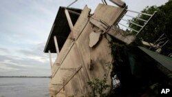 A local house damaged by floods leans toward the Mekong River in Koh Norea village in Phnom Penh, Cambodia, Thursday, Dec. 8, 2011.