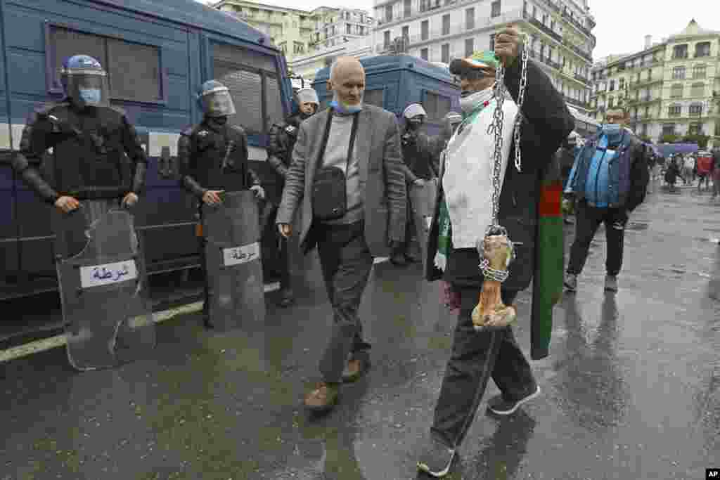 "A man holds a bone while shouting ""That's what's left for those who vote for the President"" as Algerians demonstrate in Algiers to mark the second anniversary of the Hirak movement."