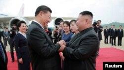 北韓領導人金正恩在平壤國際機場歡迎到訪的中國國家主席習近平。(2019年6月21日)